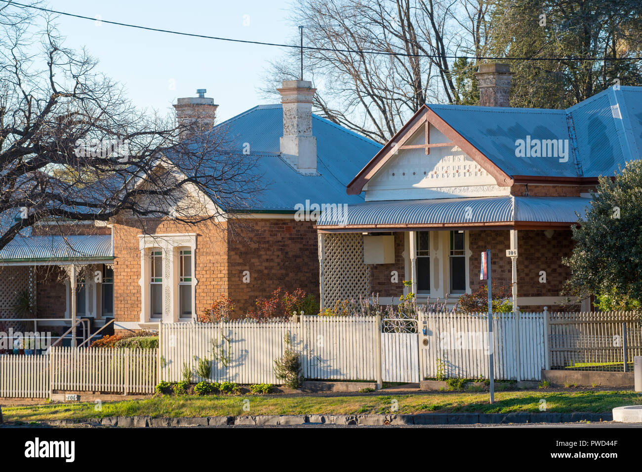 Two smaller workman Federation Bungalow design cottages with picket fences in Orange New South Wales, Australia - Stock Image