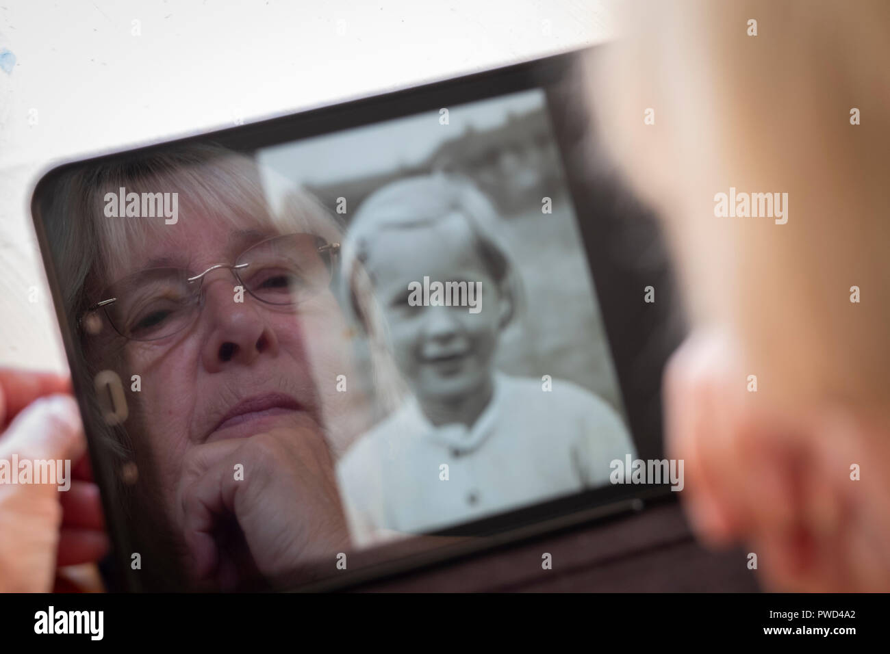 Senior caucasian woman looking at old photos of herself as a young woman on a tablet computer - Stock Image
