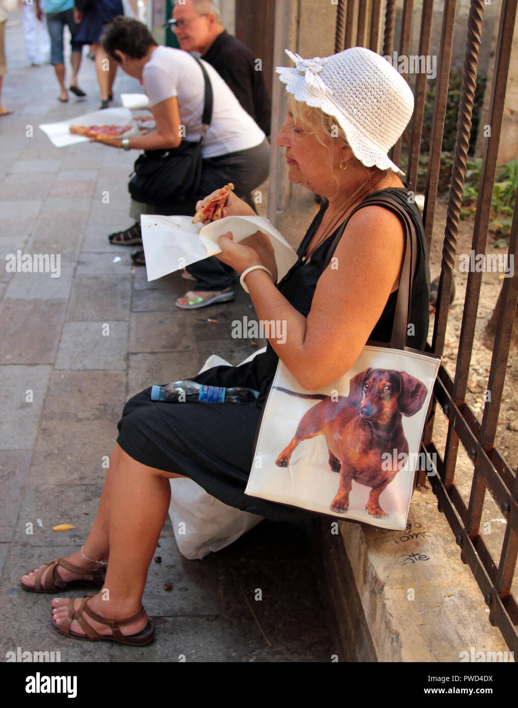 A woman is sitting on a wall enjoying a slice of pizza. She has her doggy bag ready if she cannot finish the slice. - Stock Image