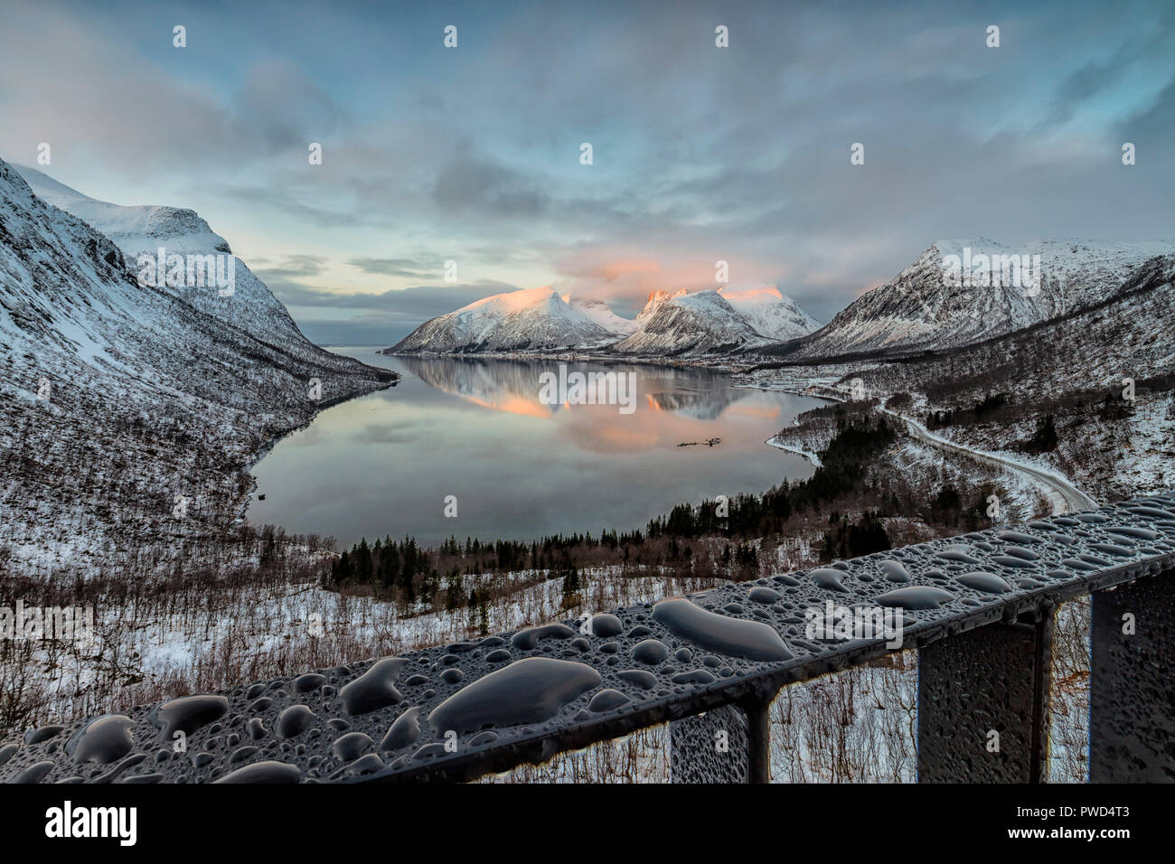 Drops of water frame the snowy peaks reflected in the cold sea at sunset Bergsbotn Senja Troms County Norway Europe - Stock Image