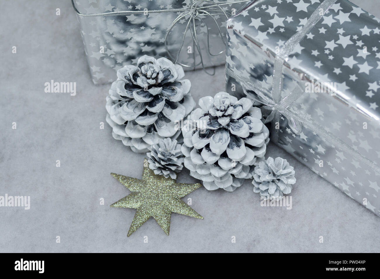 Cones in the snow and presents in silver packing - Stock Image
