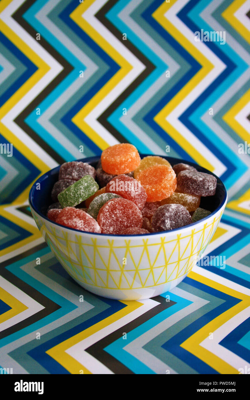 A colourful bowl of sweets/candy with a zigzag background - Stock Image
