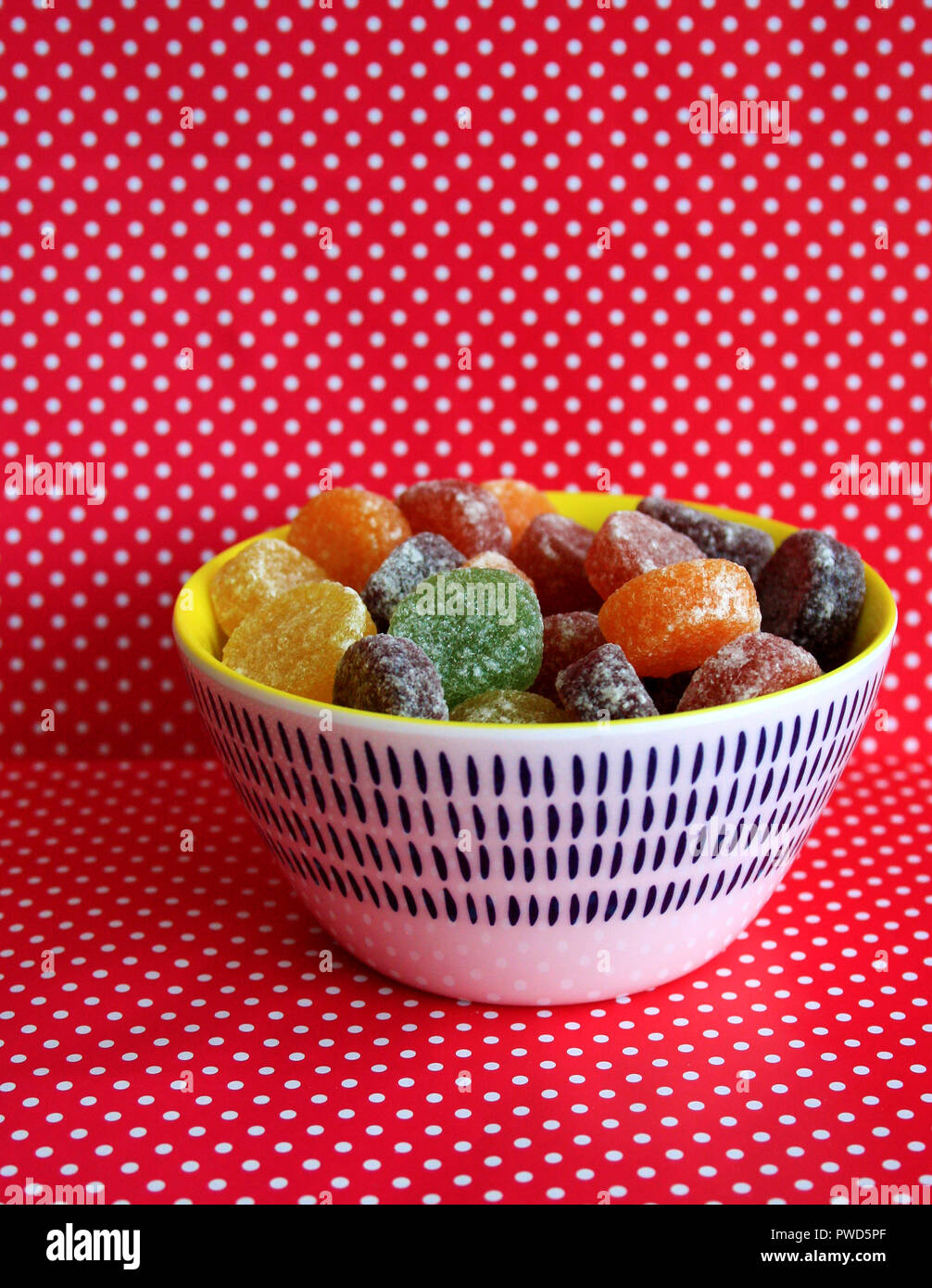 A colourful bowl of sweets/candy with a red spotted background - Stock Image