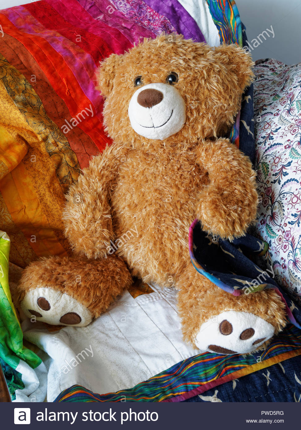 Cuddly teddy bear, with colourful blanket - Stock Image
