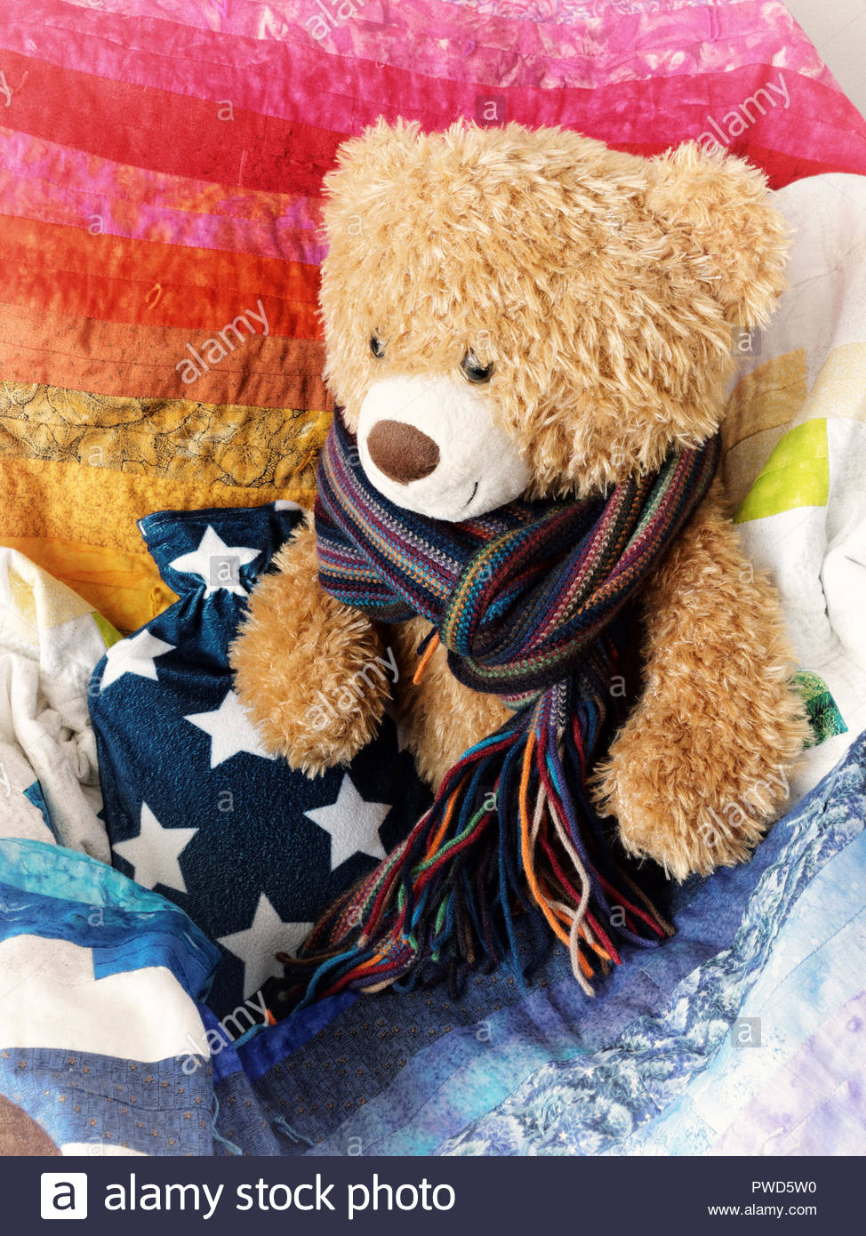 Abstract image of cuddly teddy bear, with hot water bottle, scarf and colourful blanket - Stock Image