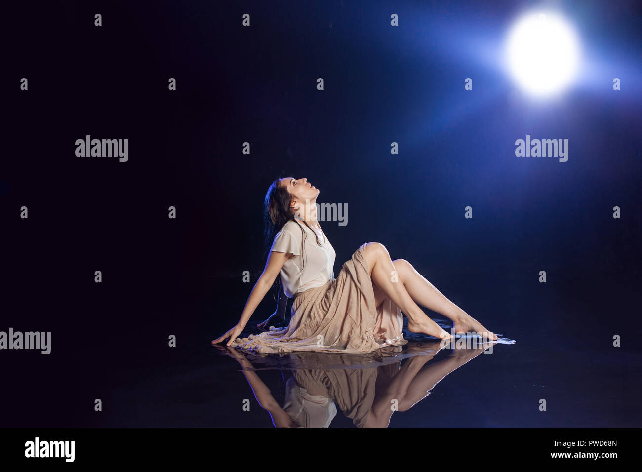 Girl sitting in the rain, night concept. Mystical style Stock Photo
