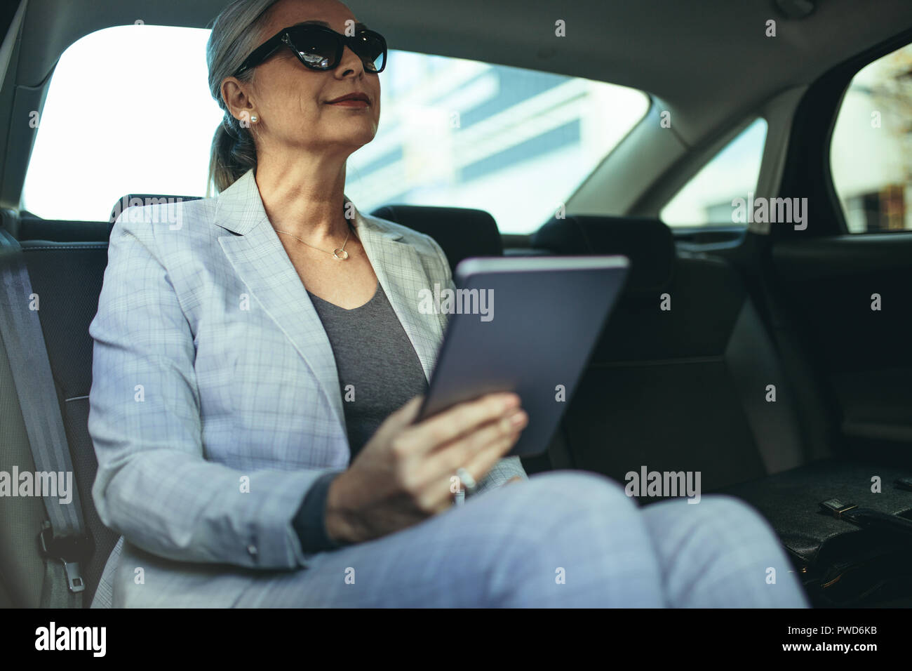 Female entrepreneur travelling to office in a luxurious car sitting on backseat with digital tablet. Senior businesswoman in car with tablet pc. - Stock Image