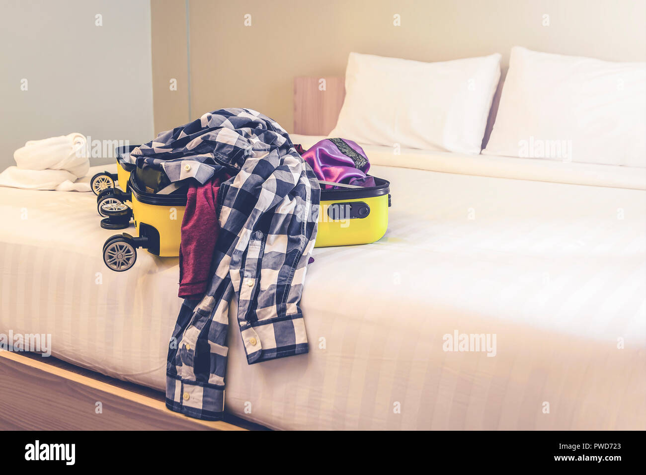 Open travel suitcase with clothes and accessories on bed - Stock Image