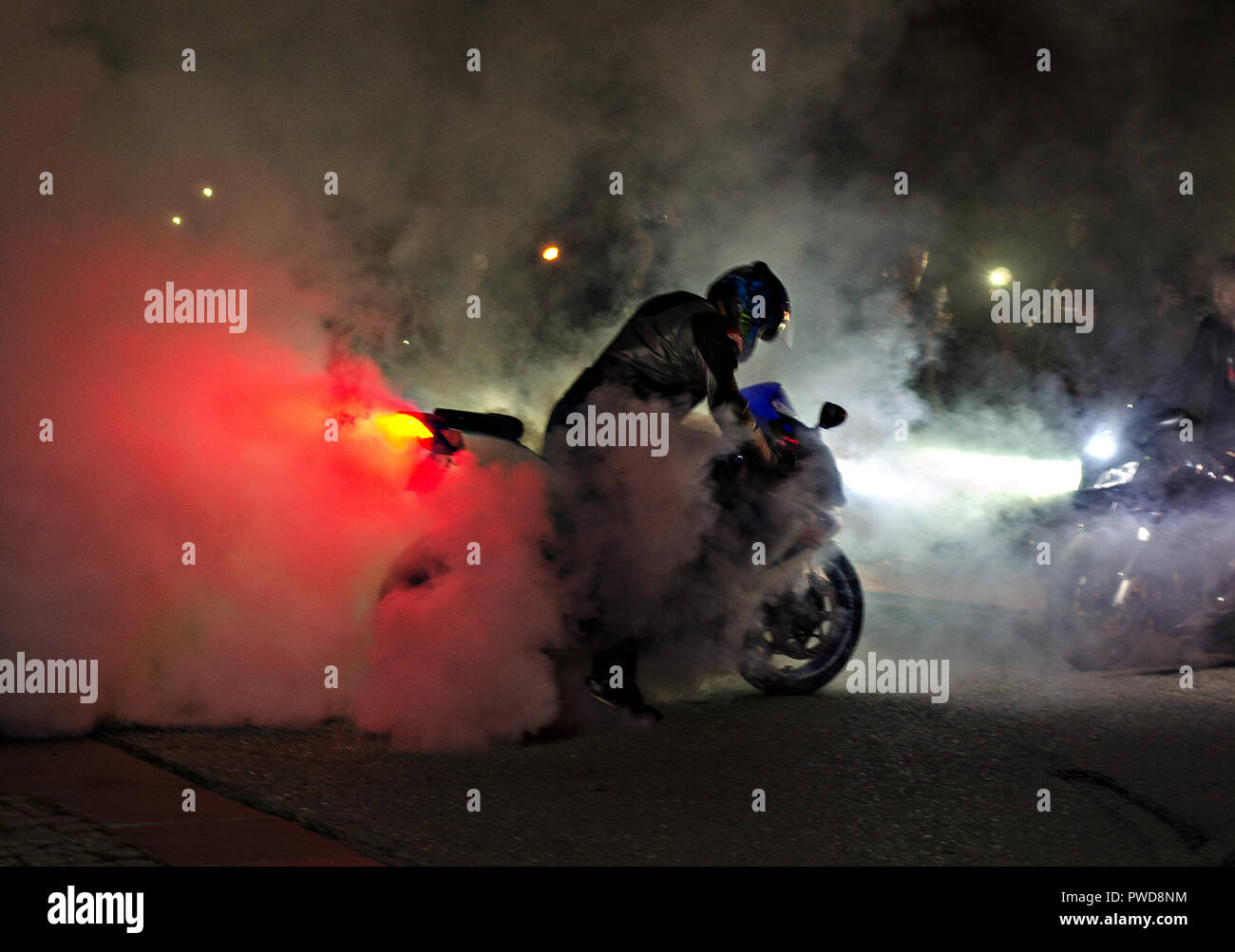 А spectacular nightly moto show with lots of smoke and a tire of tires. Many adrenalin. Red and white lighting. - Stock Image