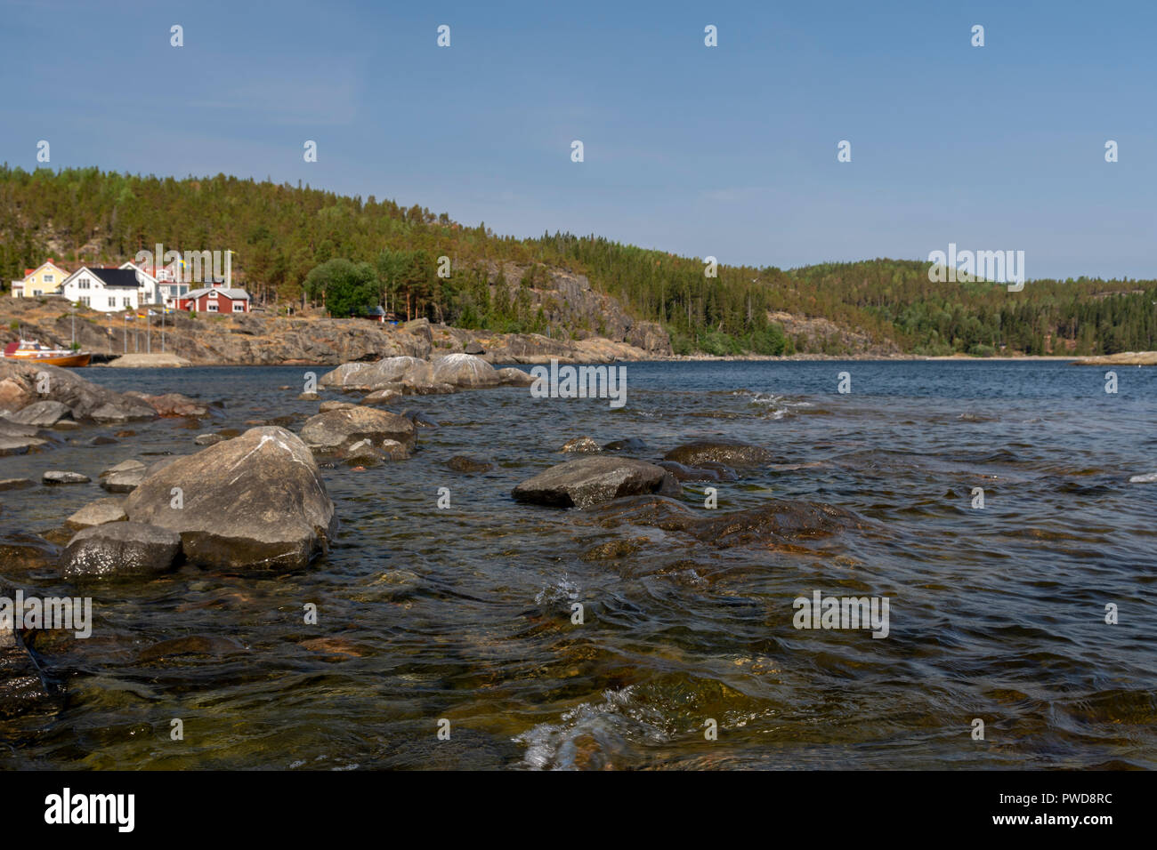 Waves and rocks in seashore in foreground and mountain with forest in background, picture from High Coast Area in Northern Sweden. - Stock Image