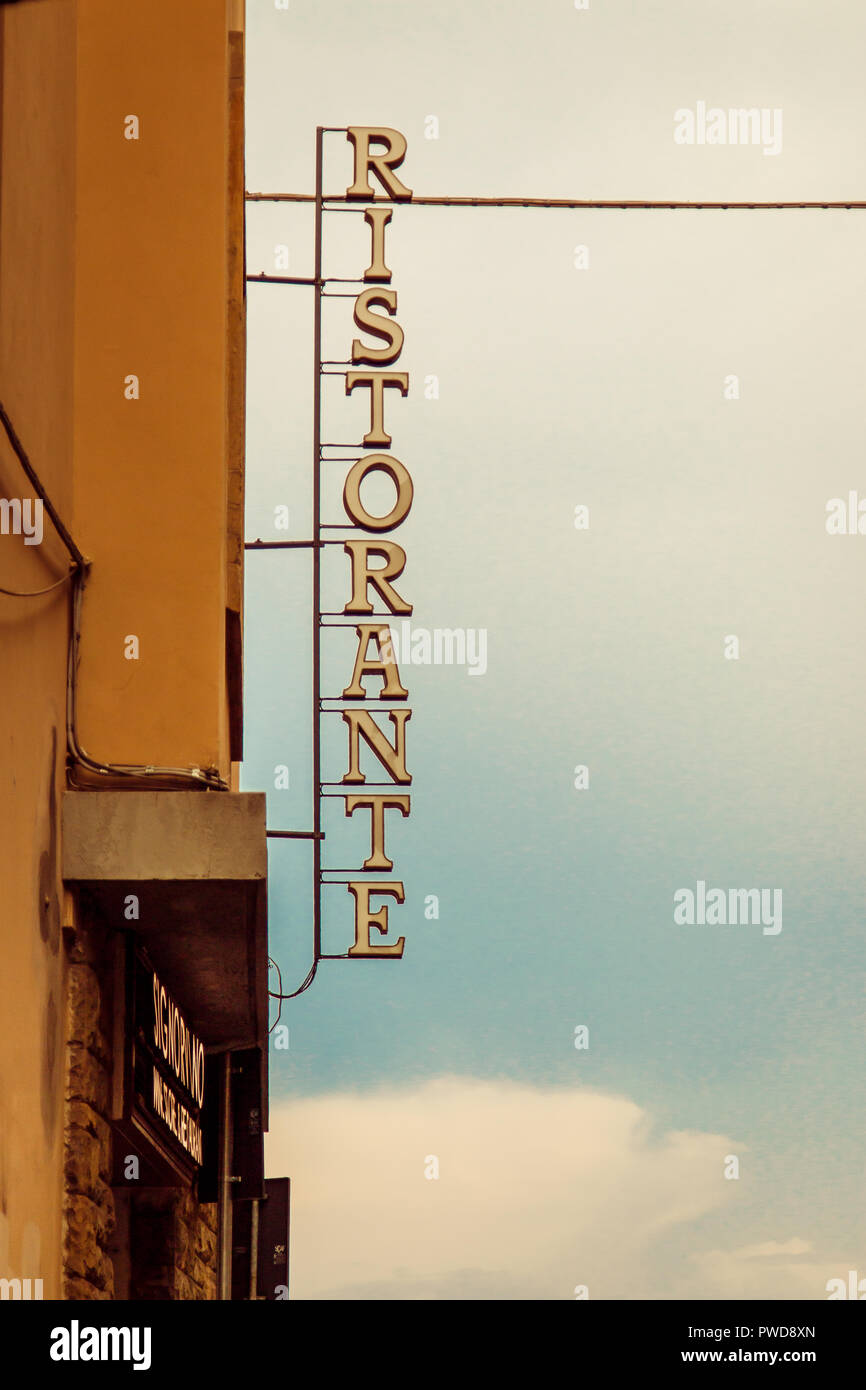 A vintage ristorante sign juts out from the side of a building in Florence, Italy. - Stock Image