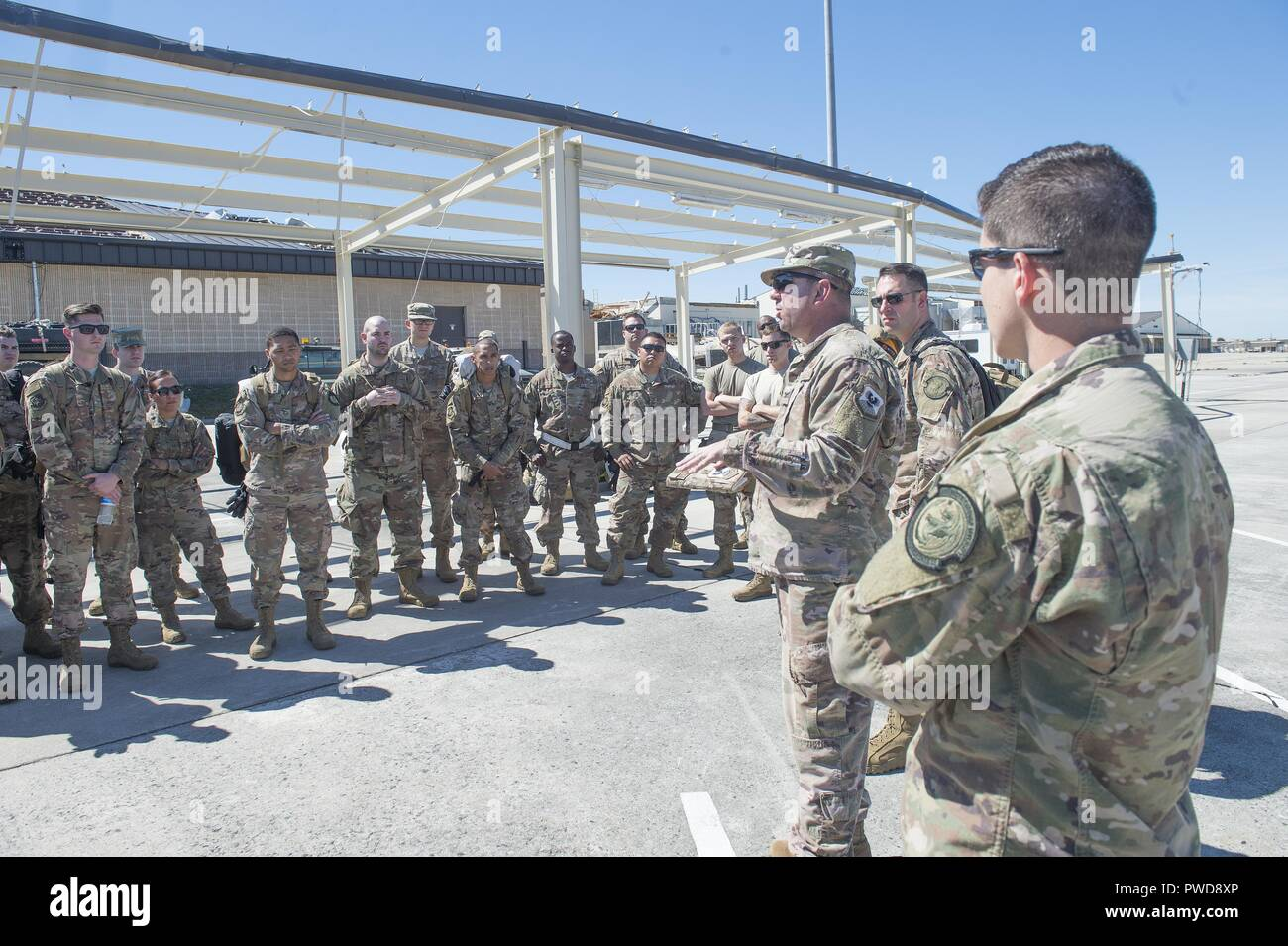 Col. Justin Niederer, 821st Contingency Response Group commander, provides an initial brief to his team prior to beginning hurricane relief operations at Tyndall Air Force Base, Florida, Oct. 12, 2018, October 12, 2018. The contingency response team deployed to assess damage and establish conditions for the re-initiation of airflow, bringing much needed equipment, supplies and personnel for the rebuilding of the base in the aftermath of Hurricane Michael. AMC equipment and personnel stand by across the nation to provide even more support upon request (U.S. Air Force photo by Tech. Sgt. Liliana - Stock Image