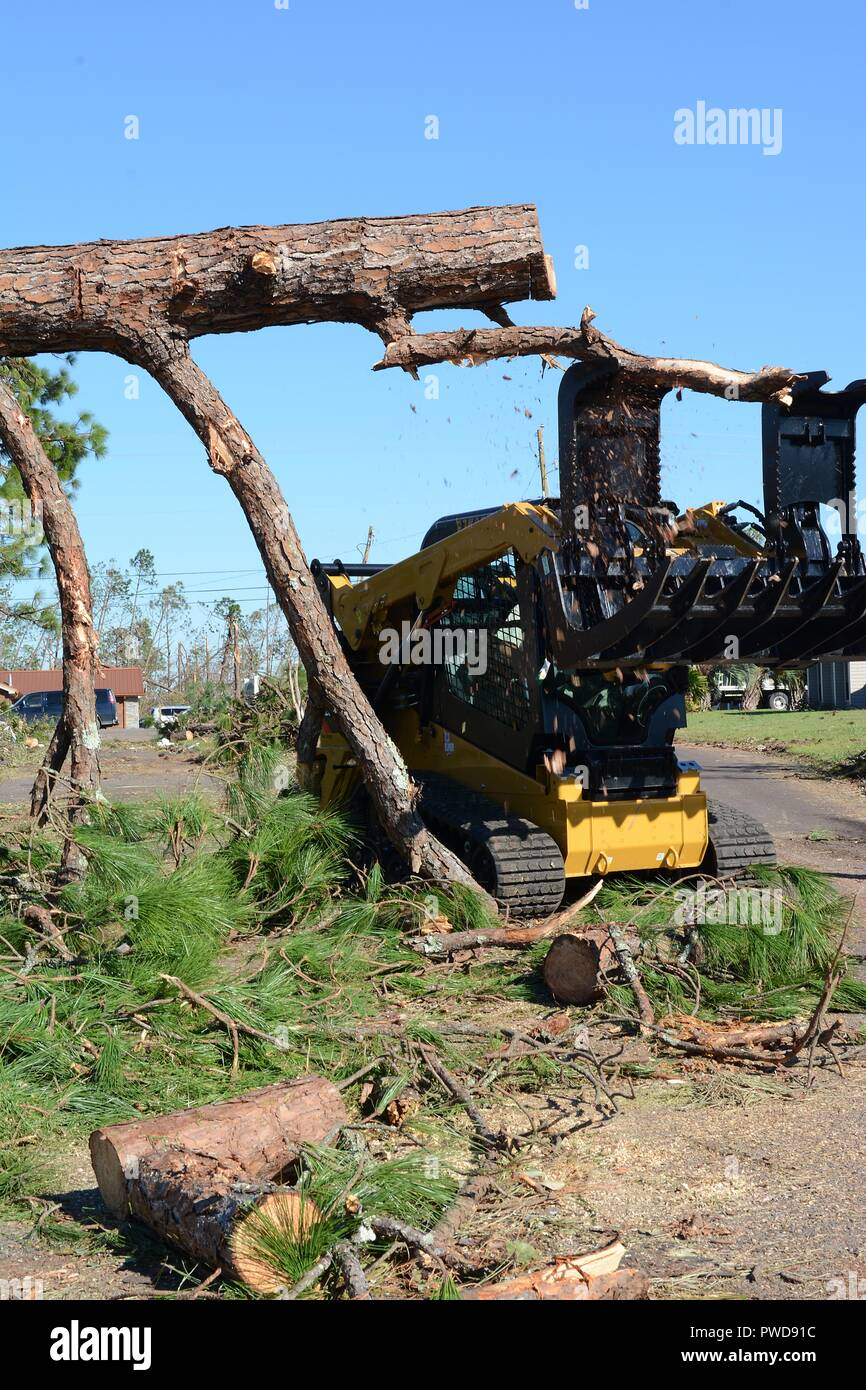 Staff Sgt. Alex Spano, electrical journeyman from the 202nd REDHORSE of Camp Blanding, Fla. uses a skid steer to clear a fallen tree blocking a residential road in Lynn Haven, Fla. Oct. 13, 2018, October 13, 2018. Hurricane Michael left heavy damage throughout the Panama City area, and the 202nd was called on for their expertise in route clearing. (U.S. Air National Guard photo by Staff Sgt. Carlynne DeVine). () - Stock Image