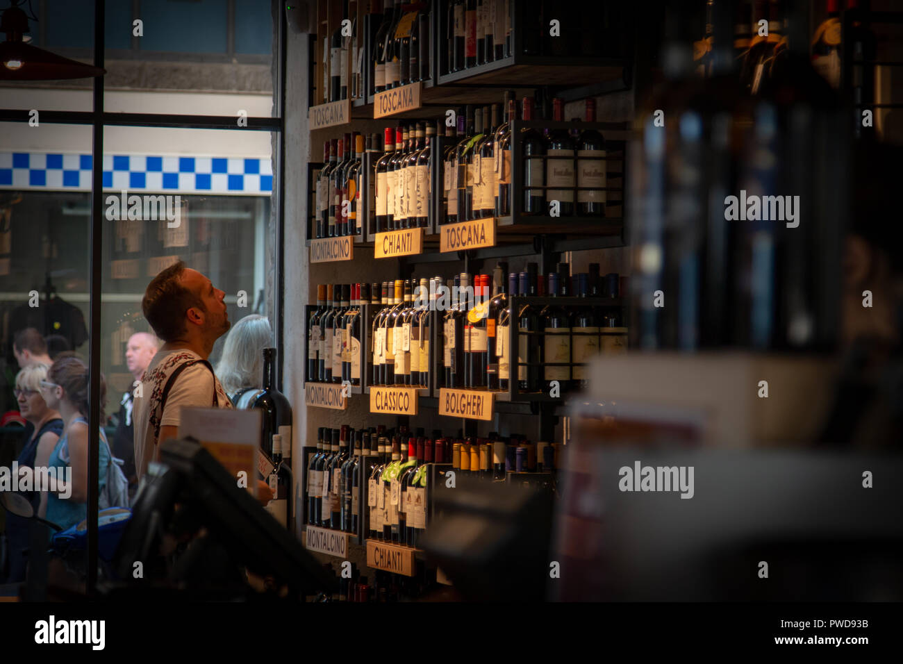 A man browses the wine choices in a shop in Florence, Italy. - Stock Image