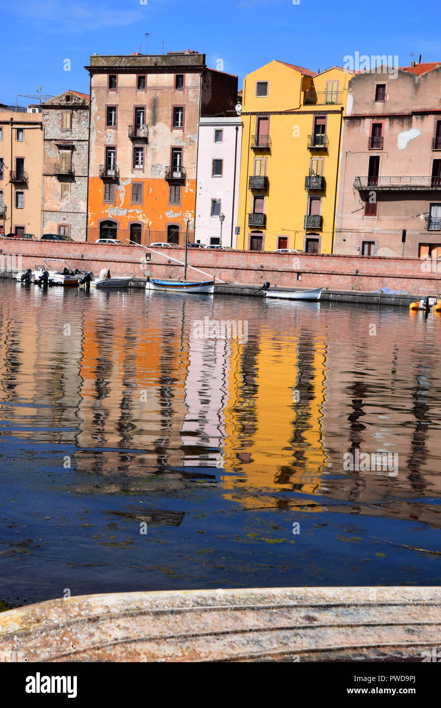 bosa river embankment, panoramic view on the boats on the river temo in Bosa in Sardinia including typical colorful Italian houses these are reflected Stock Photo
