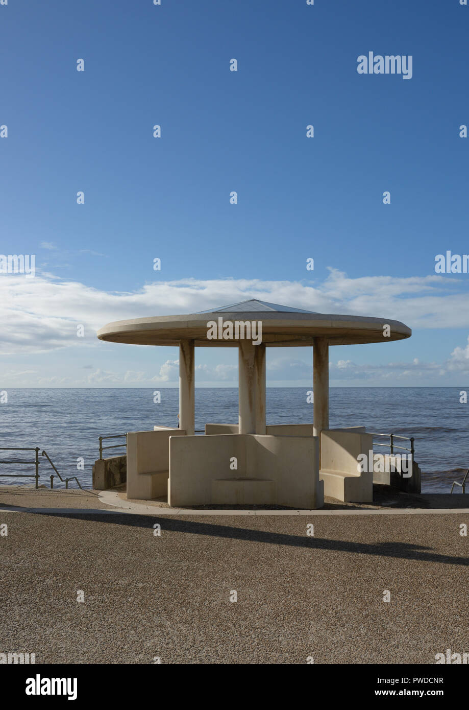 Pre cast concrete seafront shelter with curved roof on Cleveleys promenade, sunny evening light with long shadows, Fylde coast uk Stock Photo