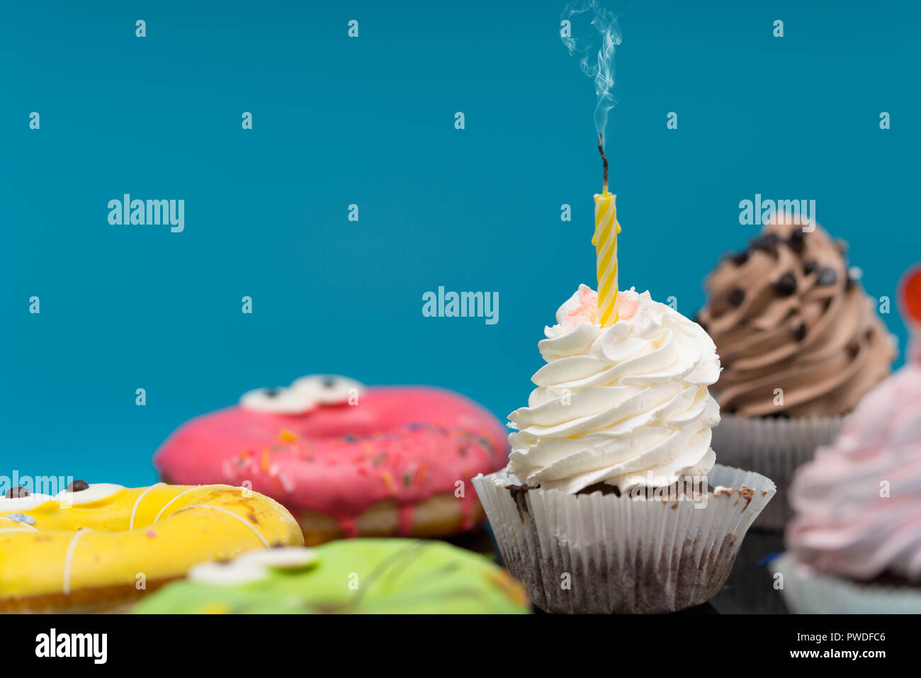 Party treats with fresh cupcakes and colorful iced ring donuts over a blue background with copy space - Stock Image