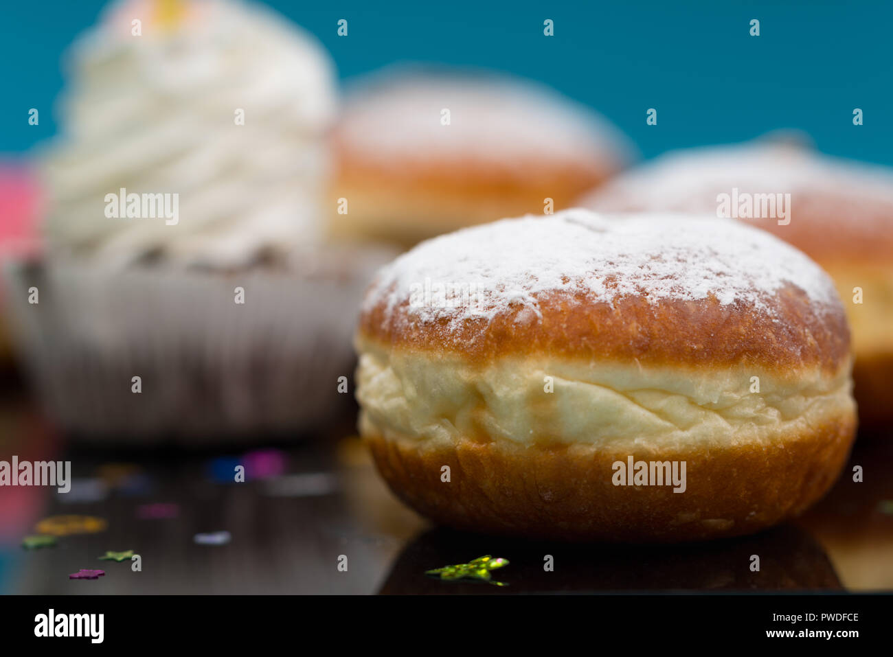 Cream bun drizzled with icing sugar on a buffet at a party with copy space in a close up view - Stock Image