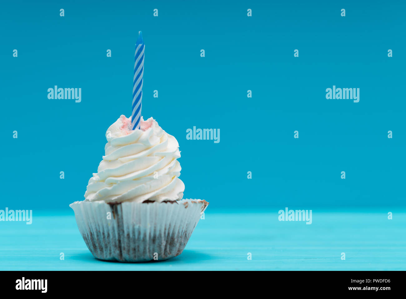 Cupcake with twirled icing and unlit candle to celebrate a birthday or anniversary over blue with copy space - Stock Image