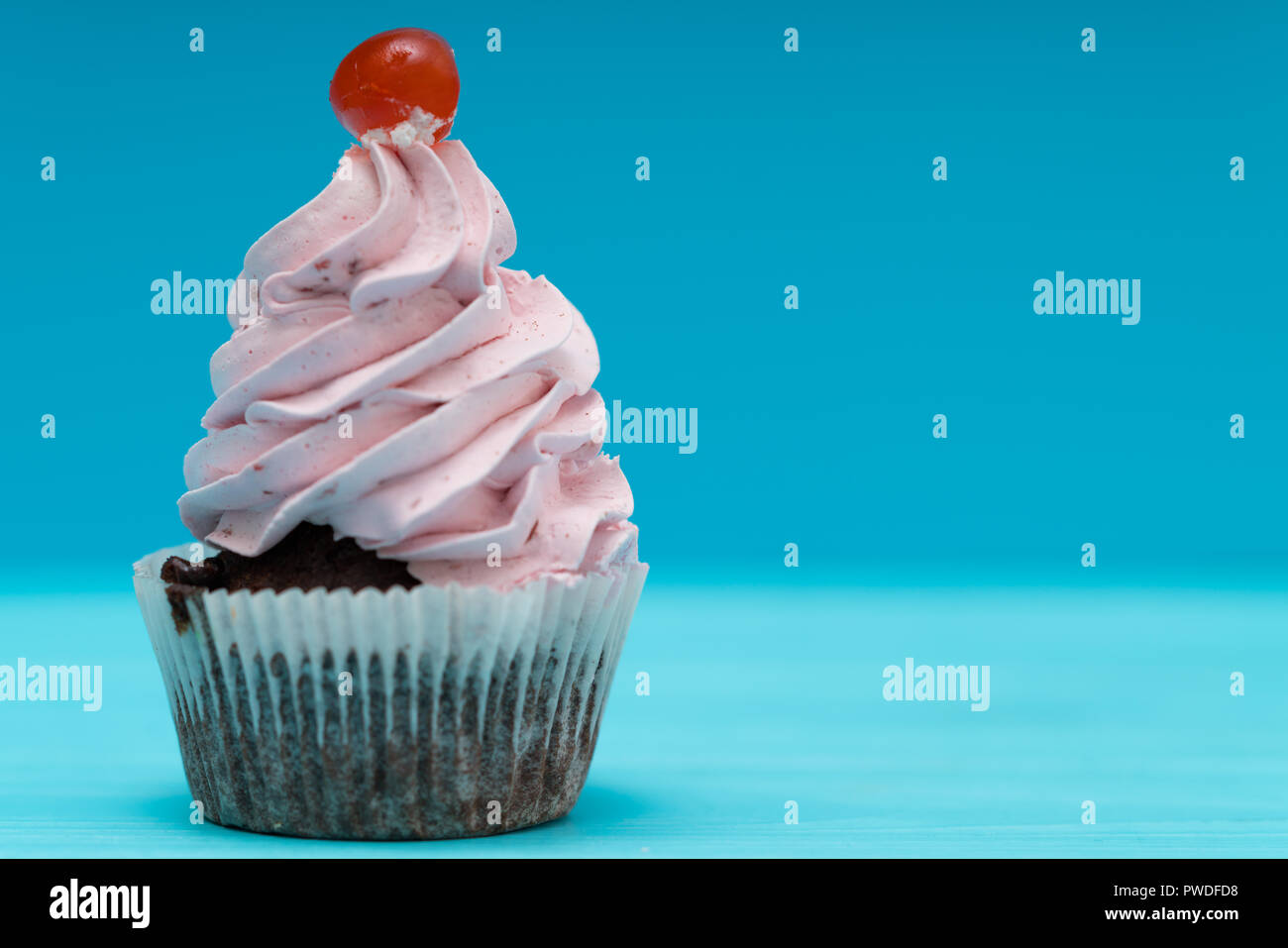 Single cupcake with twirled pink icing and cherry on a blue background with copy space - Stock Image