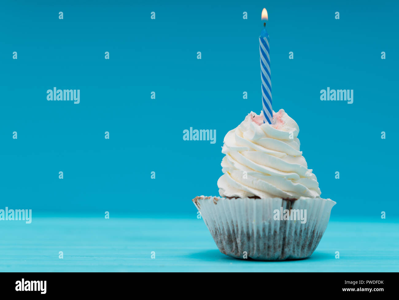 Single cupcake with twirled icing and striped blue party candle in a side view against a blue background with copy space - Stock Image