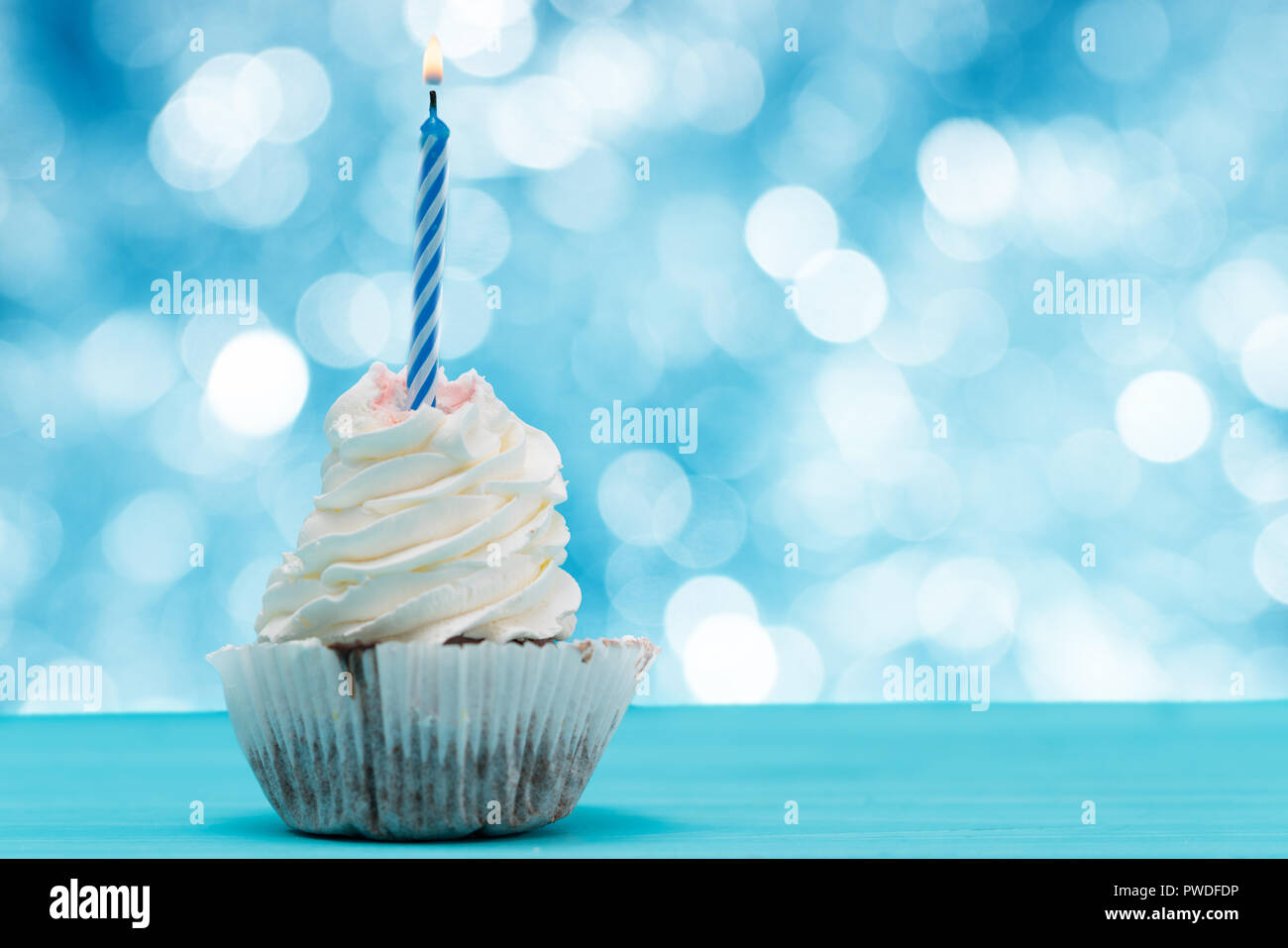 Cupcake with candle against a bokeh of sparkling party lights with copy space on a blue background - Stock Image