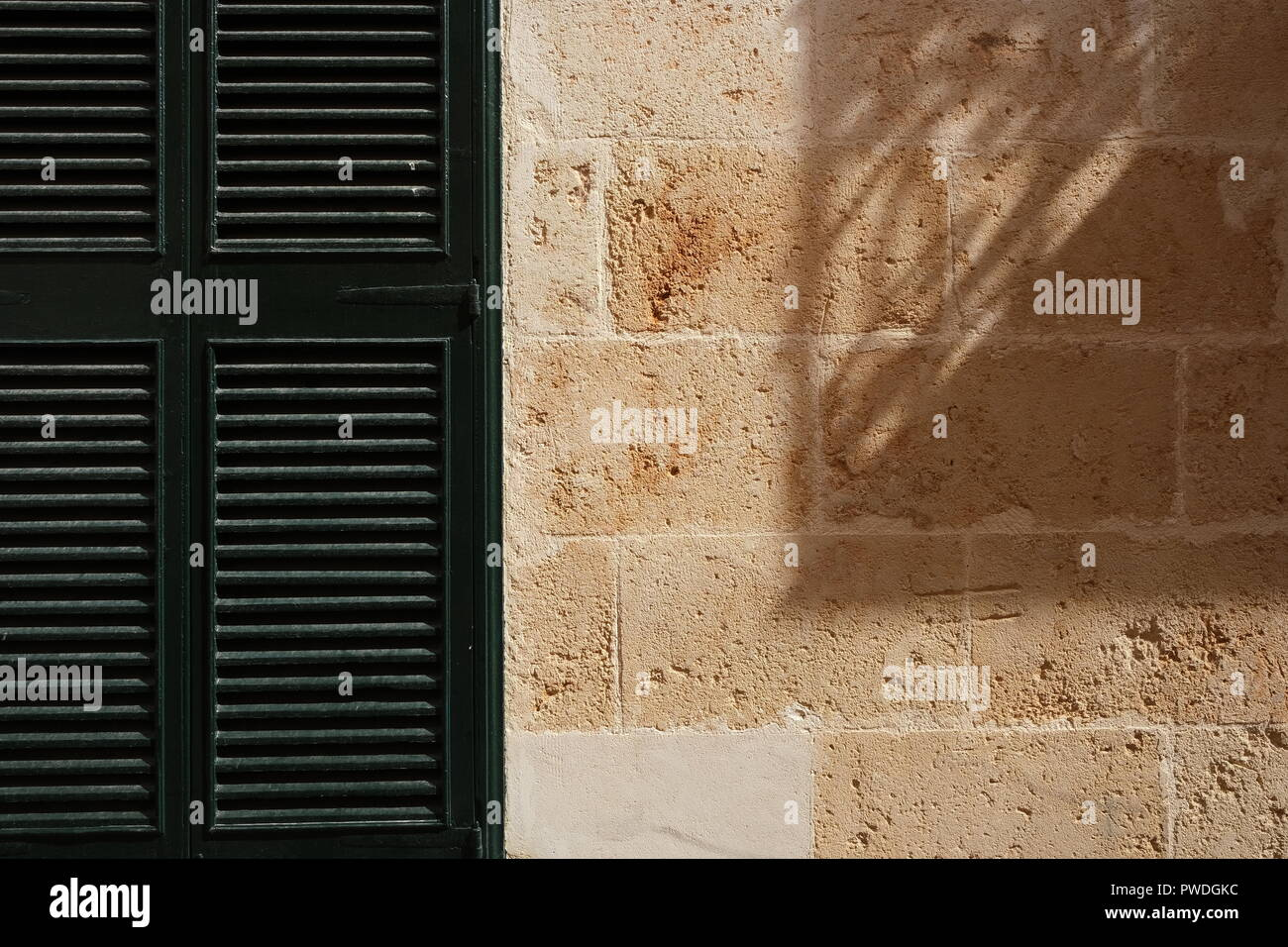 Wooden Shutter And Strong Shadow Cast On Stone Wall
