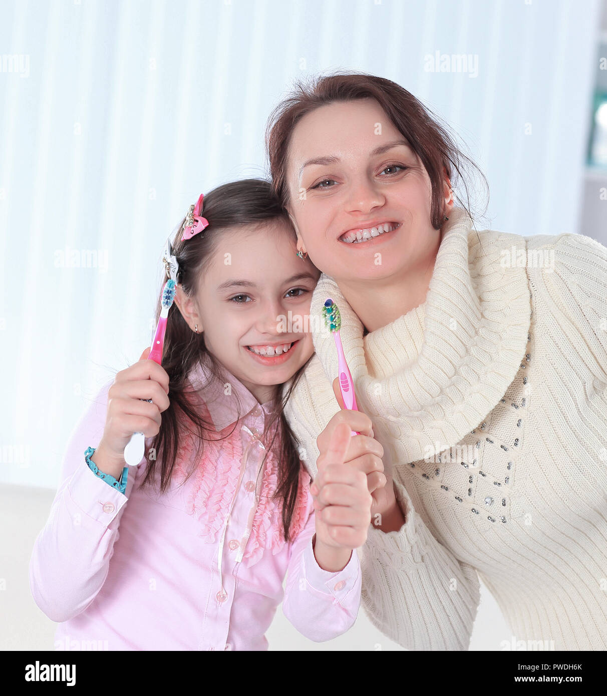 mom and daughter brushing their teeth.photo with copy space - Stock Image