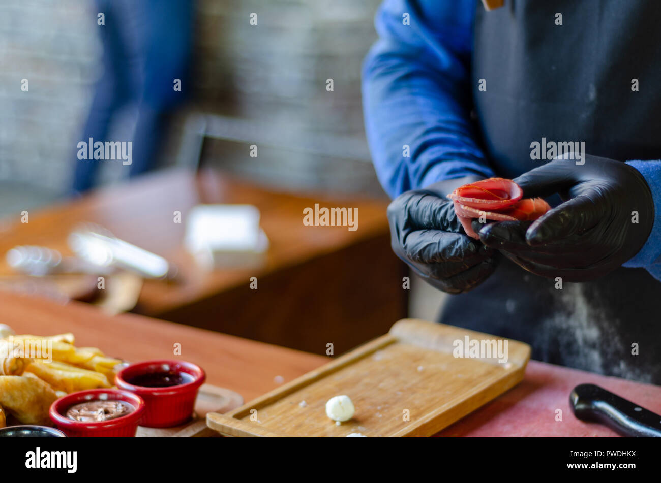 chef is preparing to put salami on the tray.Copy space,blurred background. - Stock Image