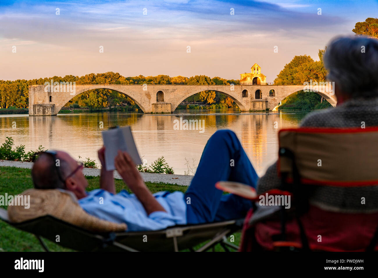 France. Vaucluse (84). Avignon. Tourists on the banks of the Rhone, in background Pont Saint-Bénézet, commonly called Pont d'Avignon - Stock Image