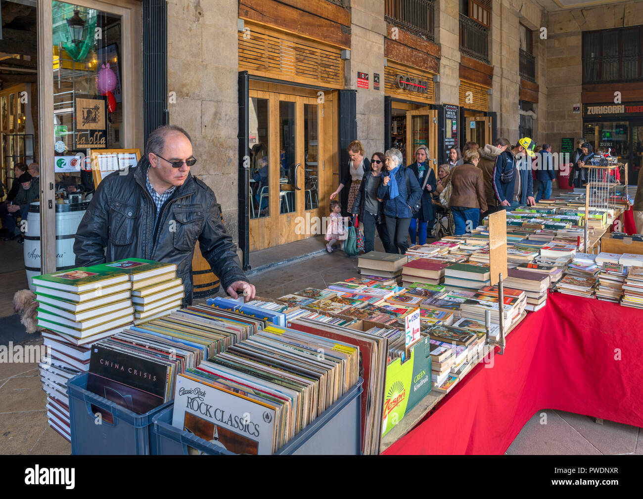 Man looking at second hand books and vinyl LP records on a market stall in Plaza Nueva, Casco Viejo, Bilbao, Basque Country, Spain - Stock Image