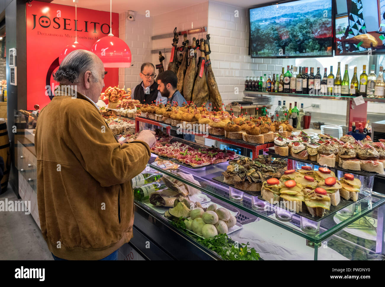 Middle aged man at a food counter in the Mercade de la Ribera, Casco Viejo, Bilbao, Basque Country, Spain - Stock Image