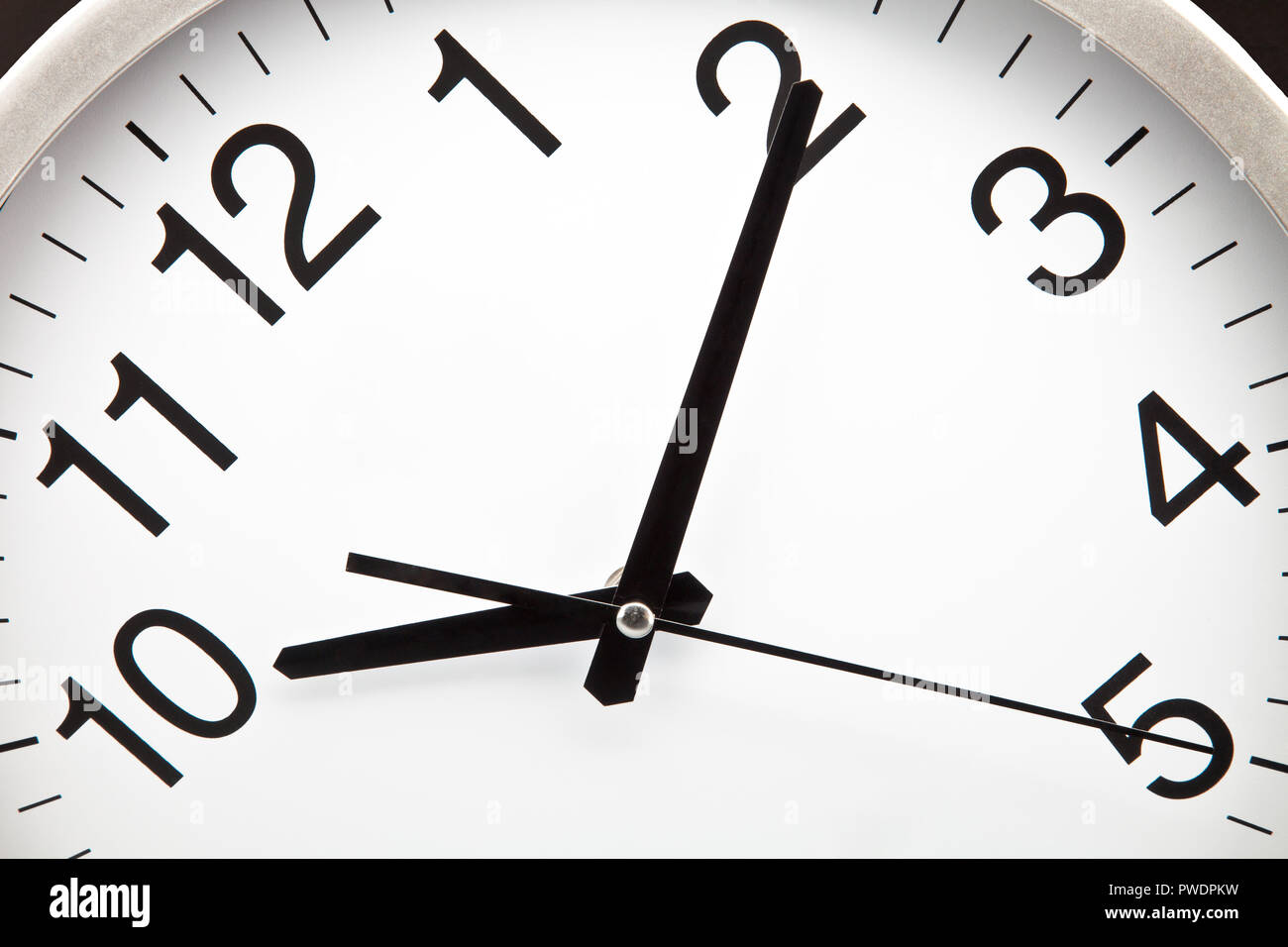 Clock with white background and black needles - Stock Image