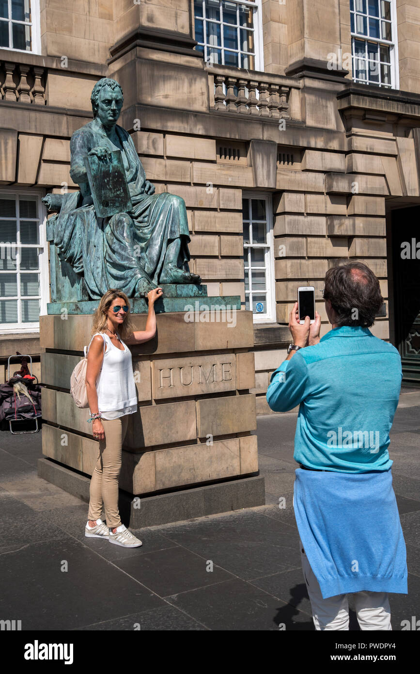 A female tourist rubs the toe on the statue of the Scottish Philosopher David Hume on Edinburgh's Royal Mile. - Stock Image