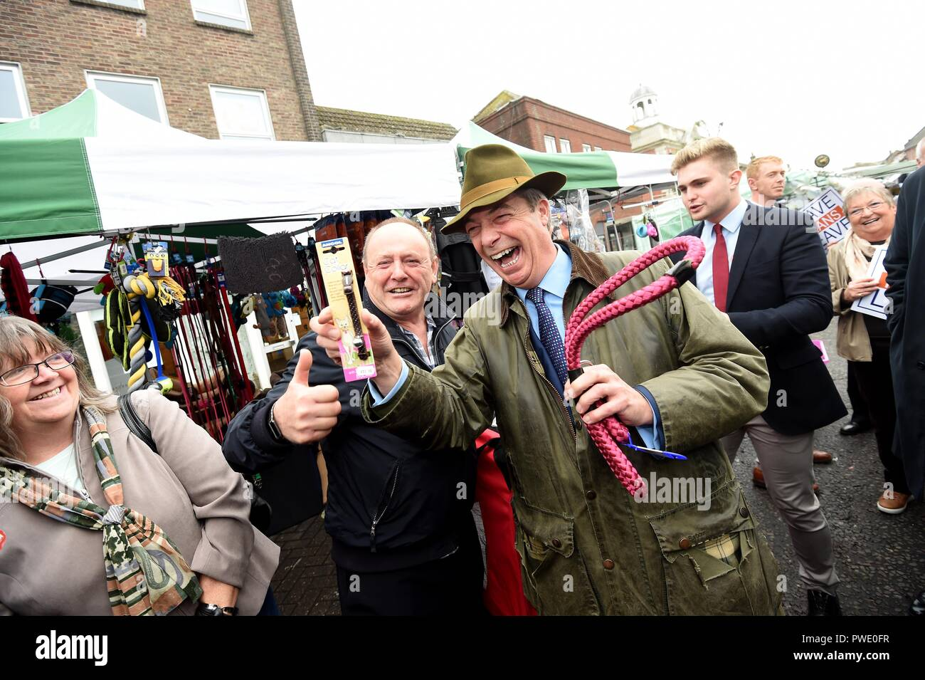 Bournemouth, UK. 15th Oct 2018. Nigel Farage MEP visits Bournemouth's Christchurch Market during the Leave Means Leave Brexit tour, UK. A stall holder gifts Nigel a leash and collar to 'control Theresa May' Credit: Finnbarr Webster/Alamy Live News - Stock Image