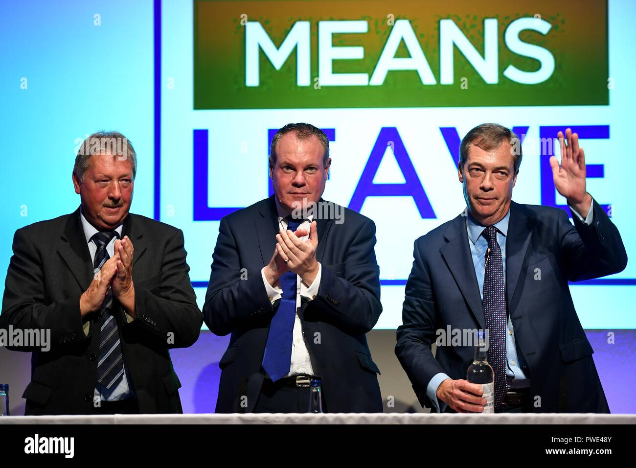 Bournemouth, UK. 15th Oct 2018. Nigel Farage MEP gives his speech at the Leave Means Leave rally to save Brexit at Bournemouth International Centre, (BIC), Dorset, UK. Pictured with DUP's Sammy Wilson MP, left and Conor Burns MP Credit: Finnbarr Webster/Alamy Live News - Stock Image