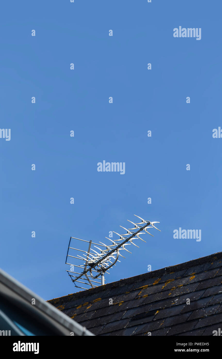 Shiny TV aerial against a blue sky. - Stock Image