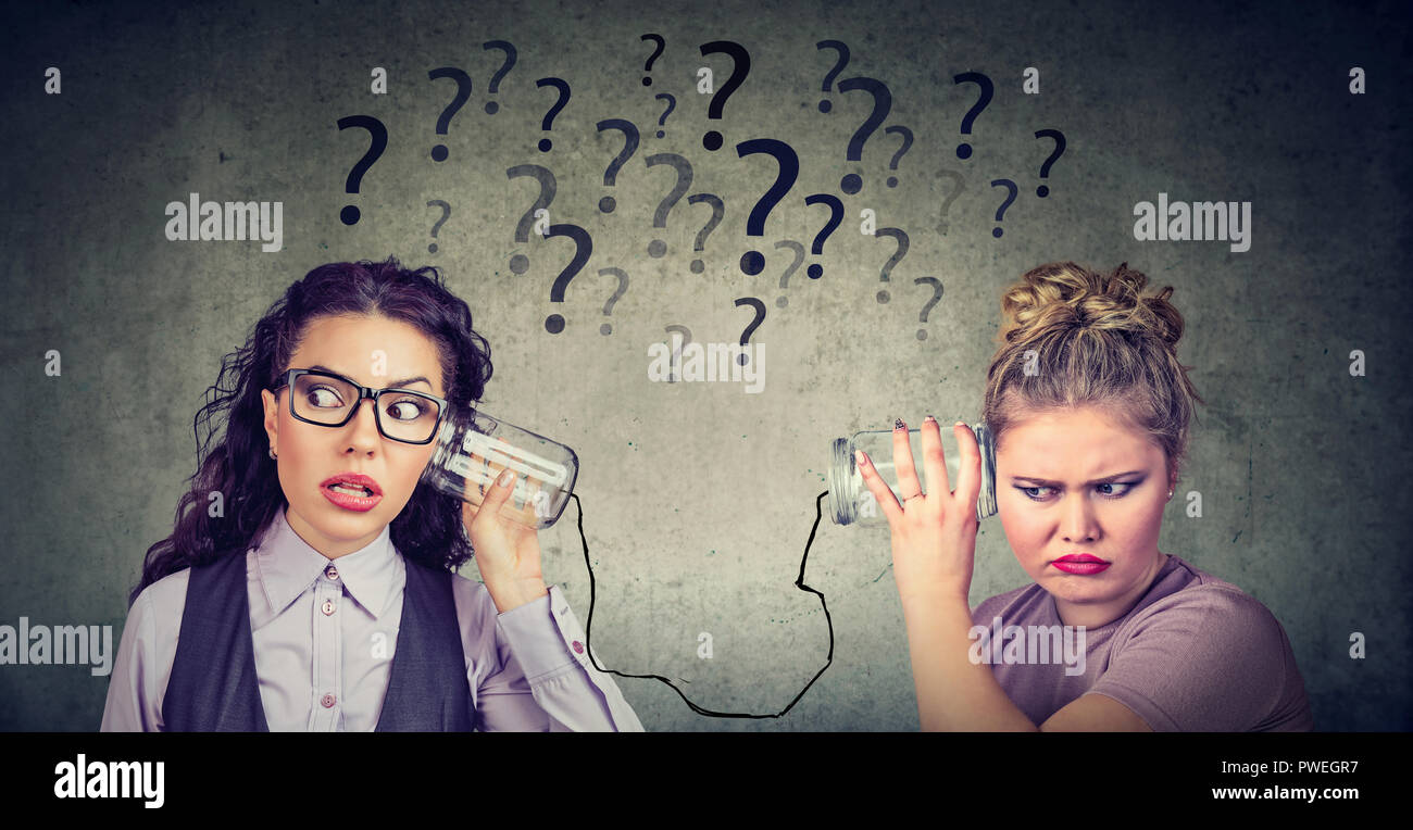 Two funny looking women having troubled communication - Stock Image