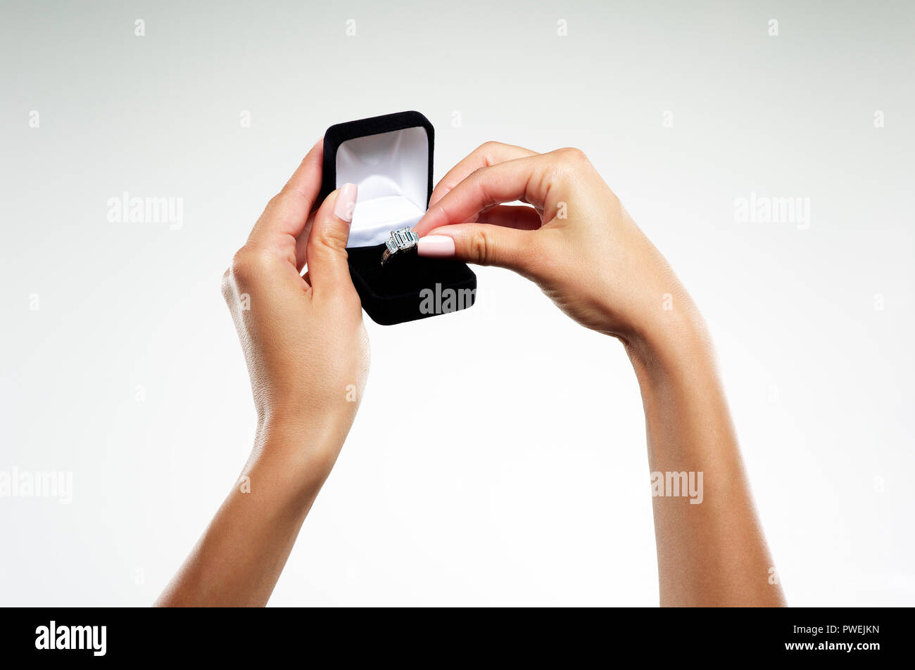 Female Model Hands with a Platinum White Gold Engagement Ring with One Emerald Cut Diamond and Baguettes in a Jewelry Box - Stock Image