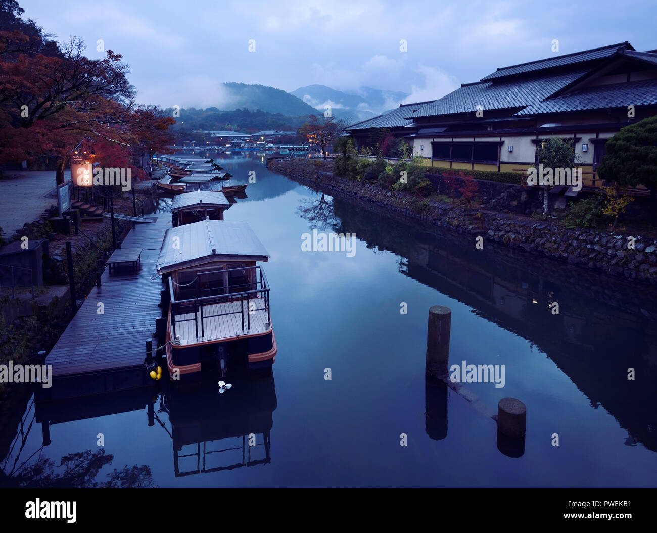 Japanese sightseeing Hoshinoya boats in a misty autumn morning scenery at Katsura River 桂川 Katsura-gawa with fog covered mountains in the background.  - Stock Image