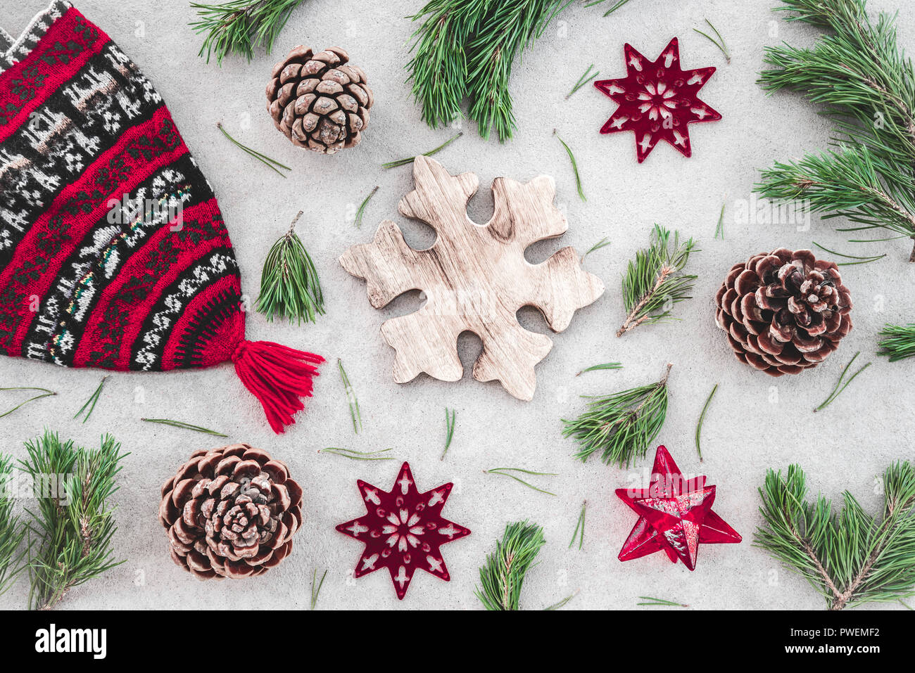 Nordic style Christmas decor. Red knitted winter hat, green pine branches, cones and stars, on concrete background. Stock Photo