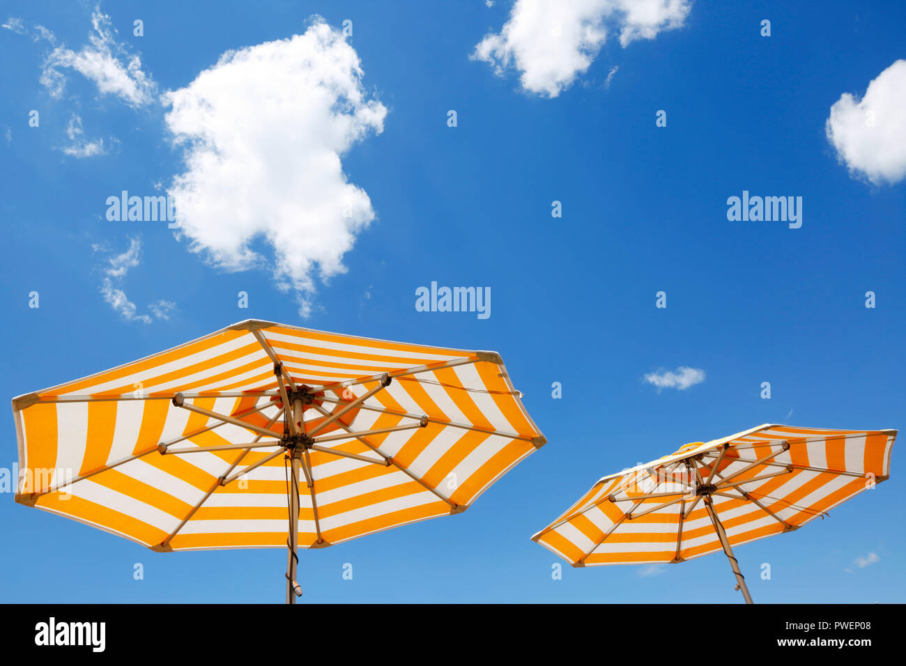 two parasols on a cruise ship against the blue sky, yellow and white, cumulus clouds, holiday, freetime, recreation, relaxation, sunlight, sunshine, shelter from sun, unpeopled, travel, cruise, tourism - Stock Image