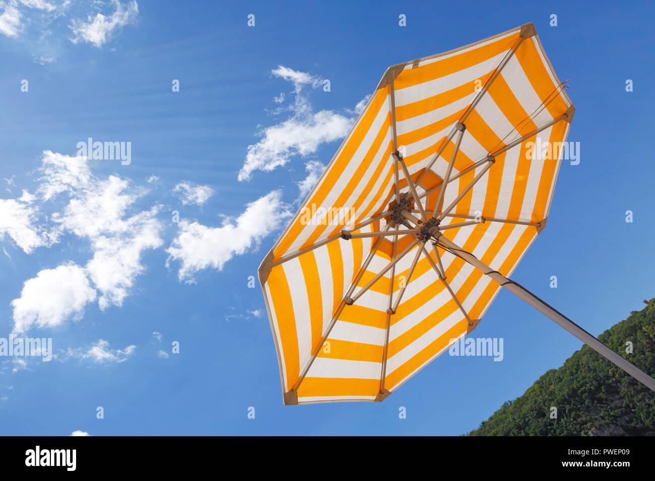 one parasol on a cruise ship against the blue sky, yellow and white, cumulus clouds, holiday, freetime, recreation, relaxation, sunlight, sunshine, shelter from sun, unpeopled, travel, cruise, tourism - Stock Image