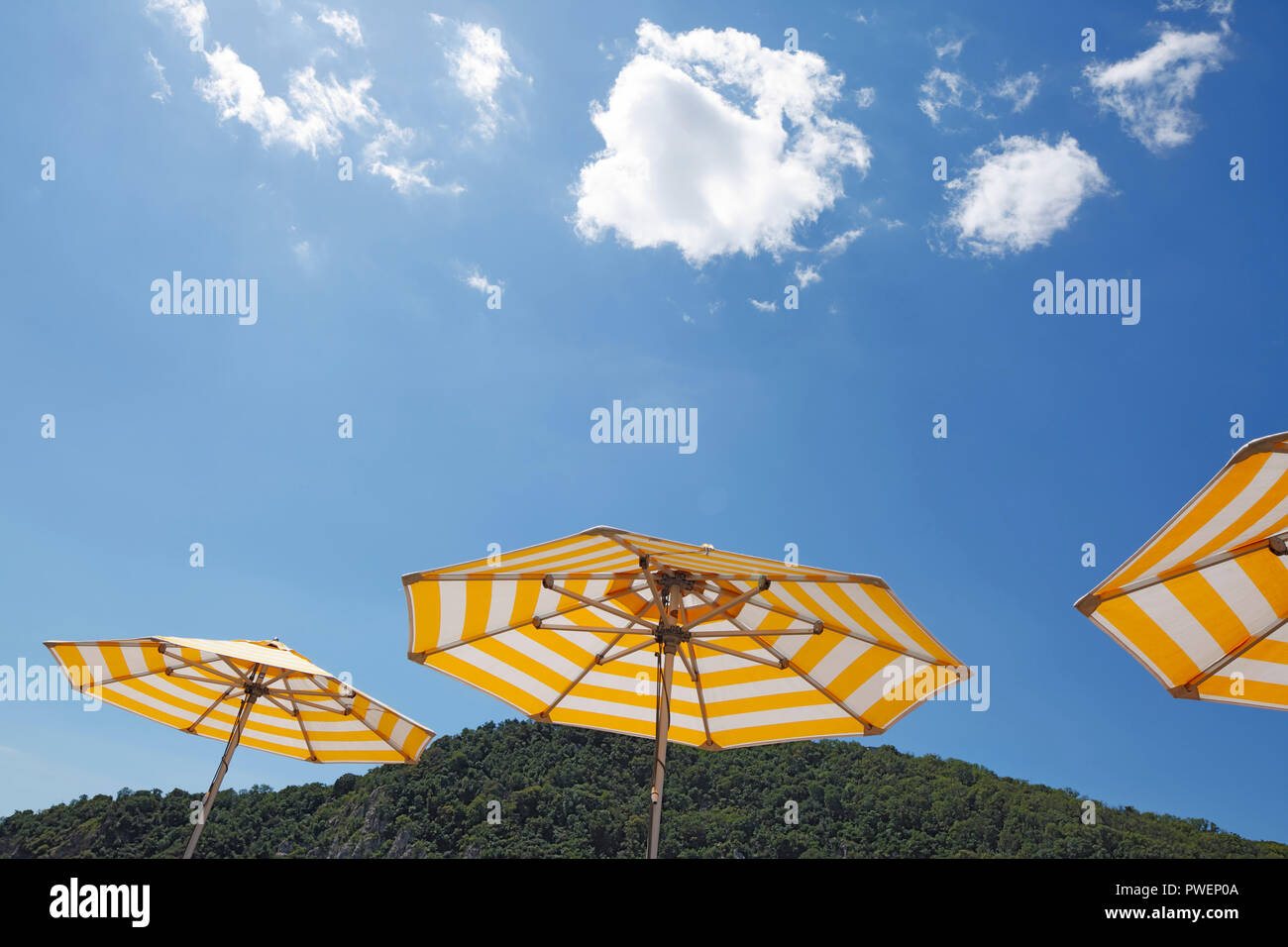 three parasols on a cruise ship against the blue sky, yellow and white, cumulus clouds, holiday, freetime, recreation, relaxation, sunlight, sunshine, shelter from sun, unpeopled, travel, cruise, tourism - Stock Image