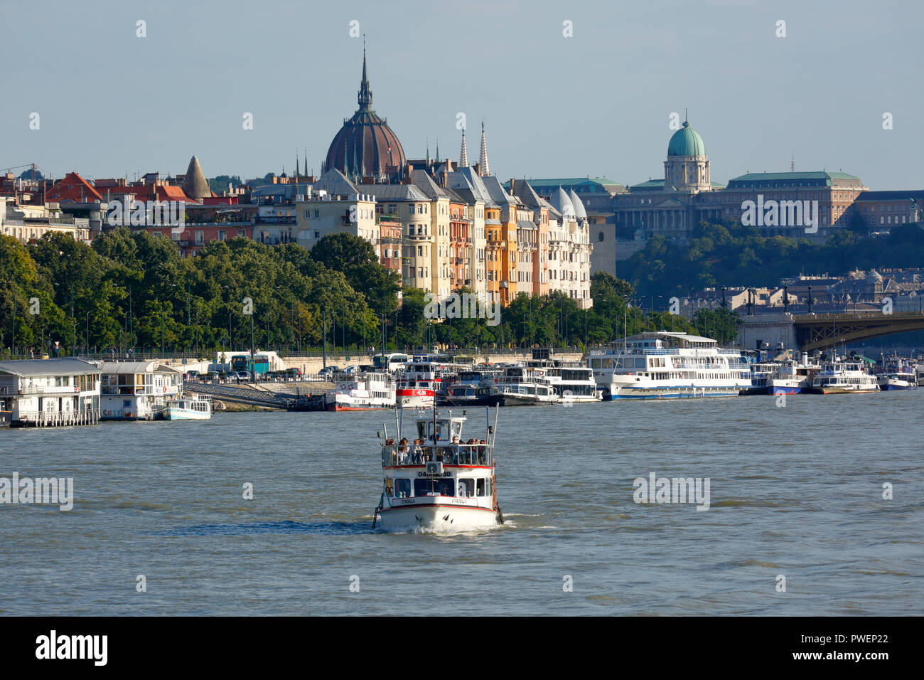 Hungary, Central Hungary, Budapest, Danube, Capital City, Danube bank of Pest, Danube landscape, business houses and residential buildings, shipping pier, ships, river navigation, left the dome of the parliament, right the Royal Palace, UNESCO World Heritage Site Stock Photo