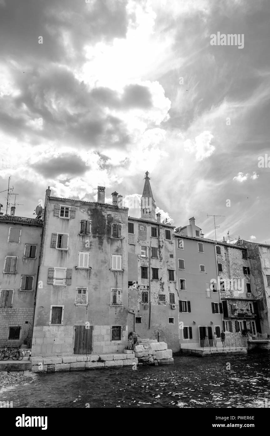 Rovinj, Croatia - June 18, 2014: Black and White photography. Waterfront buildings with people on the balconies, Adriatic Sea waters and sunrays throu - Stock Image