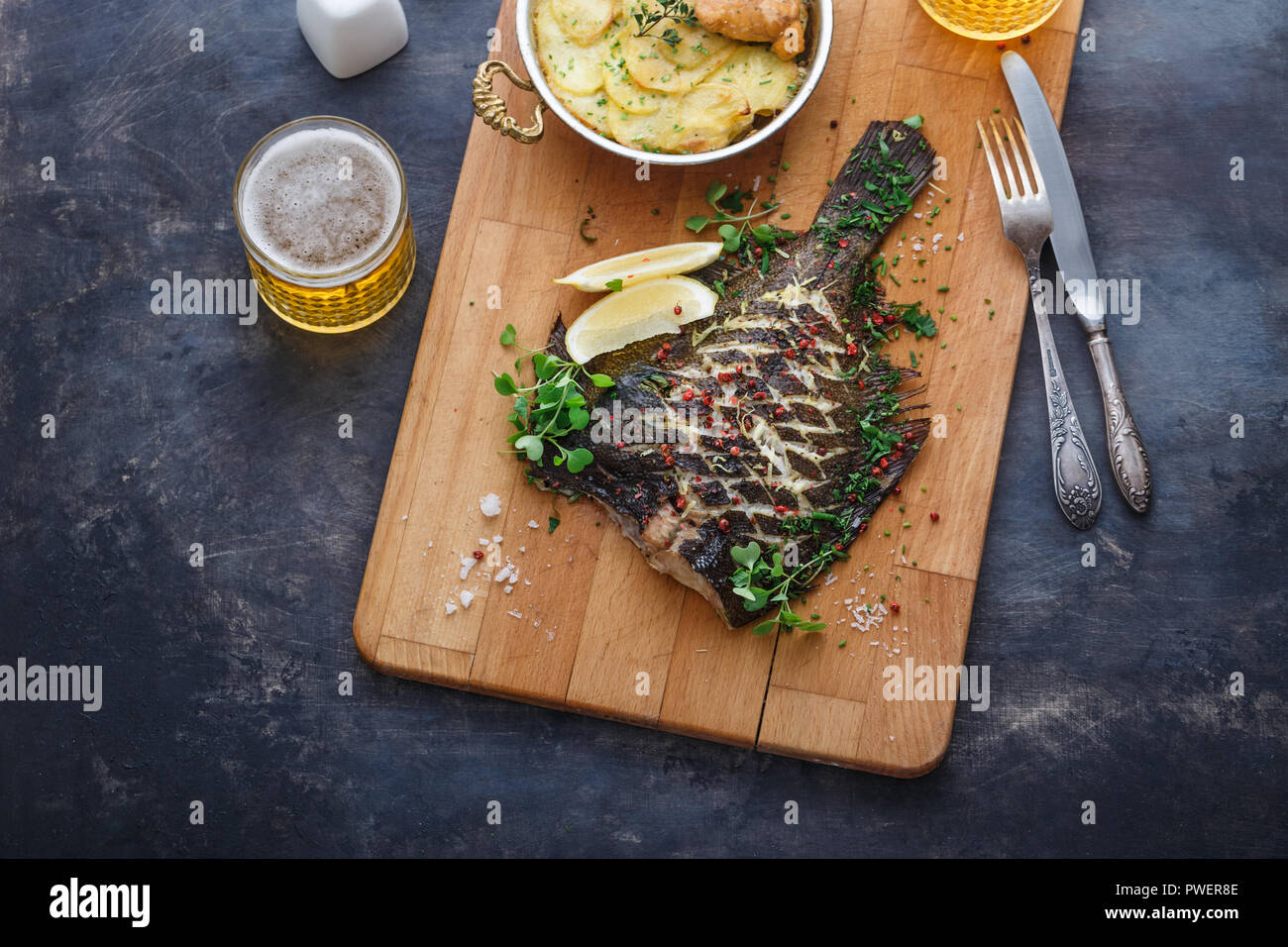 Baked flatfish with potato gratin and beer, copy space - Stock Image