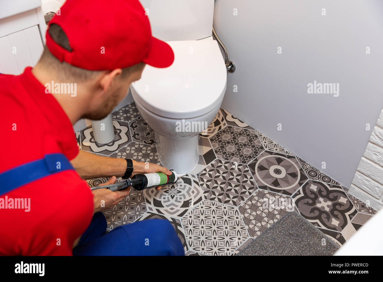 plumber applying silicone sealant around water closet - Stock Image