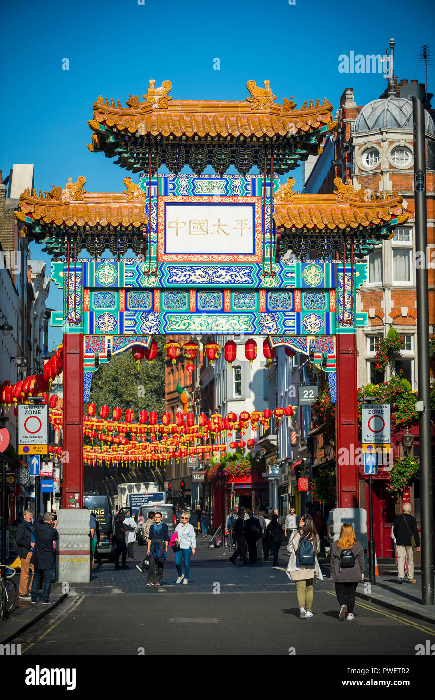 LONDON - OCTOBER 10, 2018: Decorative red lanterns hang above the street beyond a decorative gate erected in 2016 to mark the entrance to Chinatown. Stock Photo
