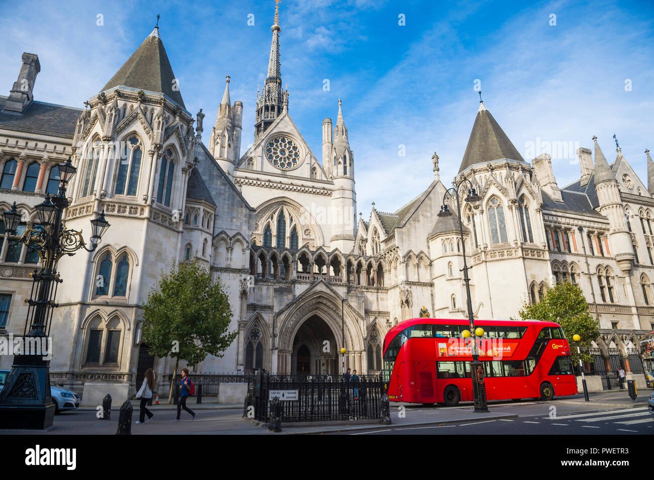 LONDON - OCTOBER 13, 2018: A modern Routemaster double-decker bus passes in front of the landmark Royal Courts of Justice on Fleet Street. Stock Photo